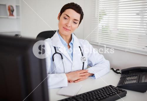 Serious female doctor looking at her computer