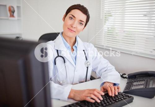 Cute female doctor typing with her computer