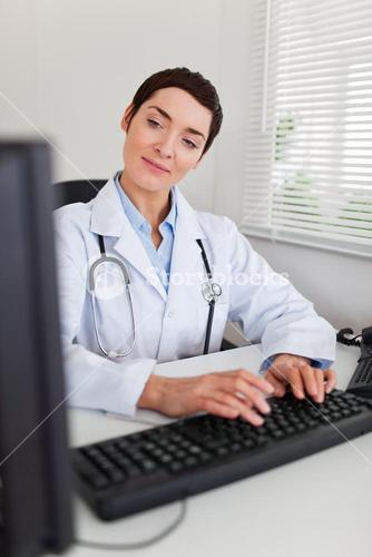 Portrait of a charming female doctor typing with her computer