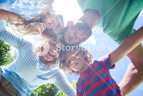 Happy parents with children forming huddle at yard