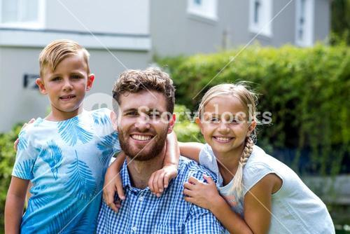 Portrait of smiling father with children at yard