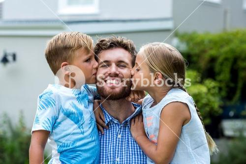 Children kissing smiling father at yard