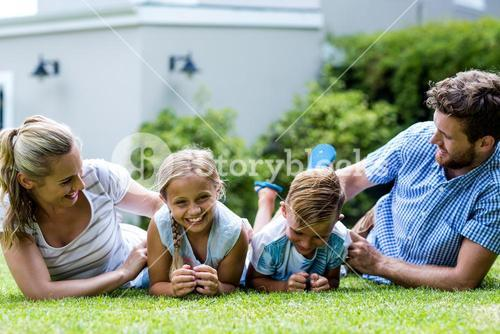 Happy parents tickling children in yard
