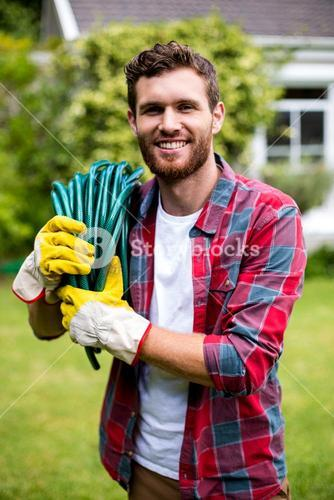 Smiling man carrying garden hose in yard