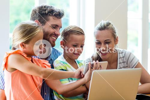Children showing phone to parents sitting with laptop at table