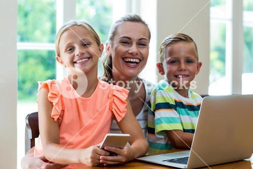 Smiling mother with children holding technologies