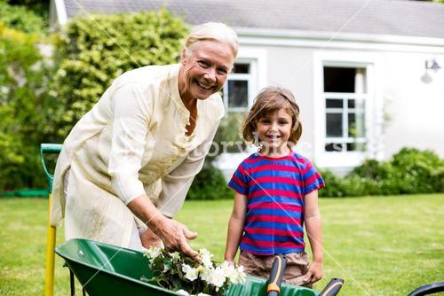 Garndmother and boy with flower pots in wheelbarrow