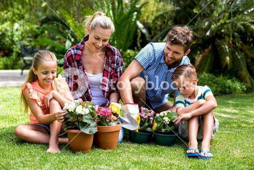 Happy family with flower pots at yard