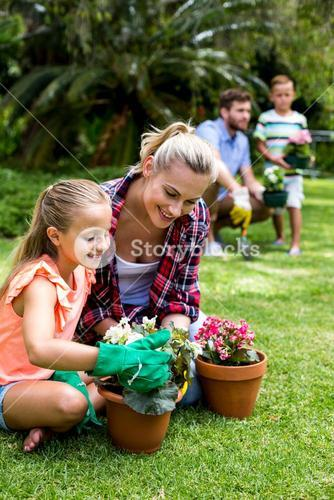 Mother with daughter holding flower pots at yard