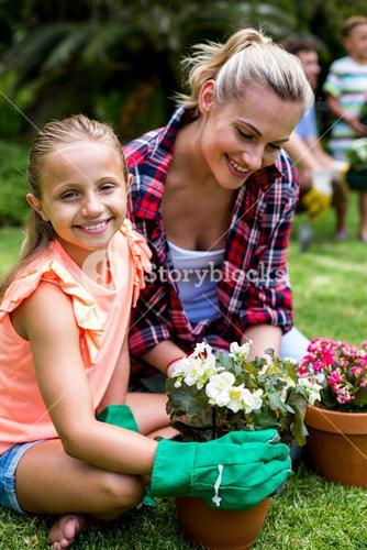 Daughter with mother holding flower pots at yard