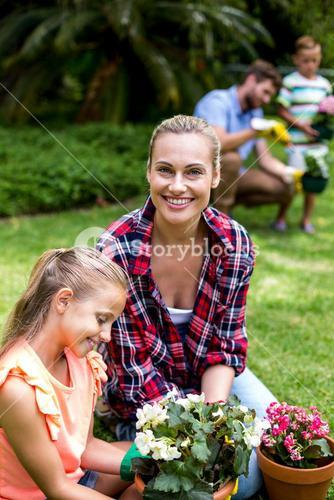 Mother helping daughter with flower pots in yard