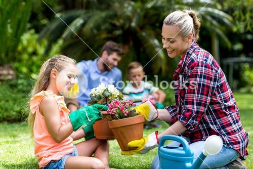 Mother and daughter with flower pots sitting in yard