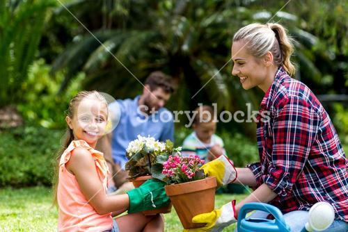 Mother giving flower pot to smiling daughter at yard