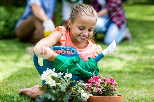 Girl holding watering can by flower pots at yard