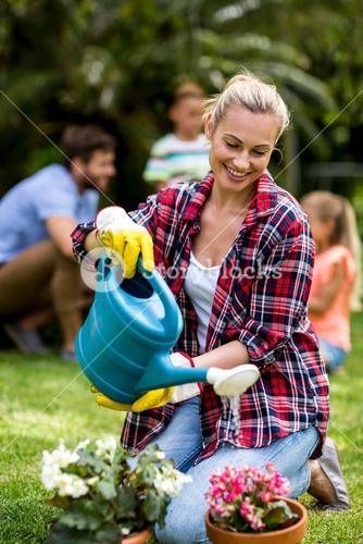 Woman watering flowers on grass at yard