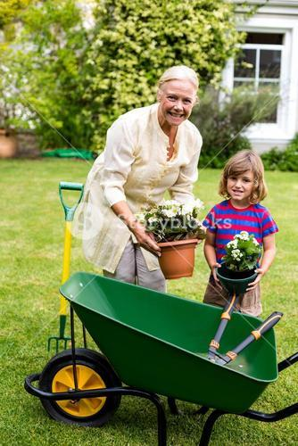 Grandmother with boy holding flower pots at yard