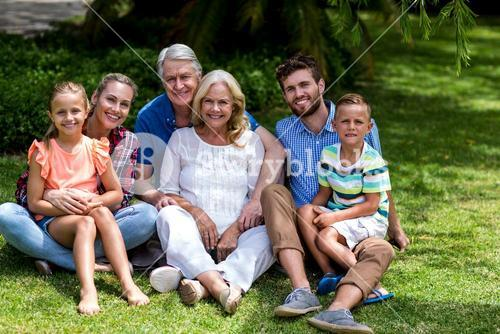Multi generation family relaxing on grass at yard