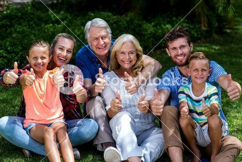 Potrait of family gesturing thumbs up at yard