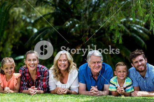 Portrait of family lying on grass at yard