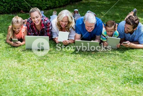 Happy family with technologies lying in yard