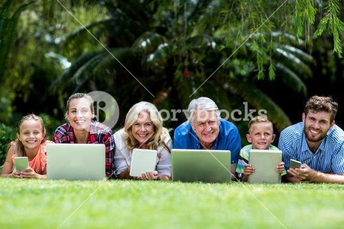 Portrait of family with technologies lying at yard