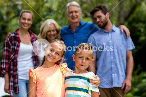Multi-generation family standing in yard