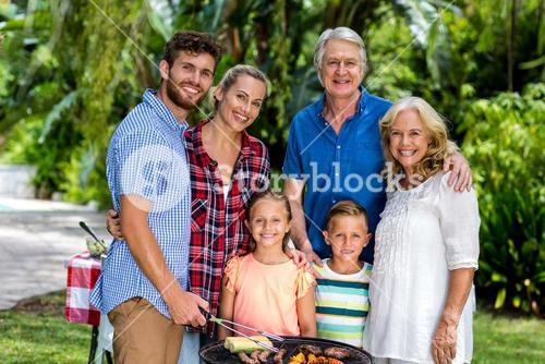 Happy family grilling food in barbeque at yard