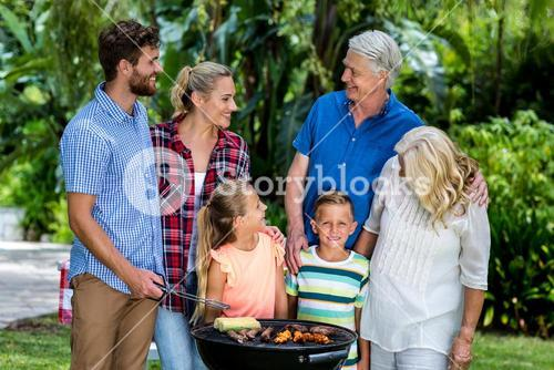 Family grilling food in barbeque at yard