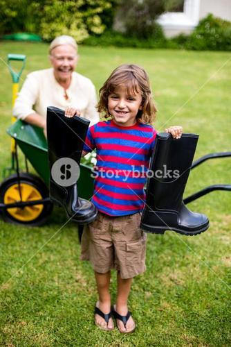Boy with wellington boots while standing in yard
