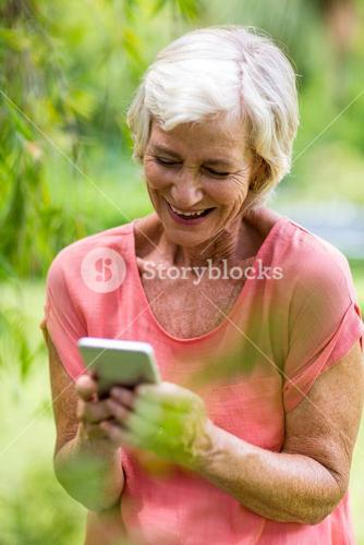 Senior woman holding phone in yard