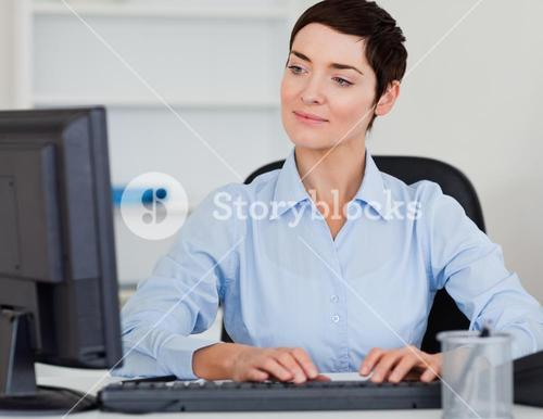 Cute businesswoman typing with her computer
