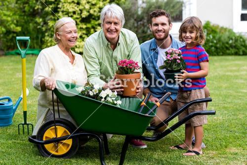Multi generation family with gardening tools in yard