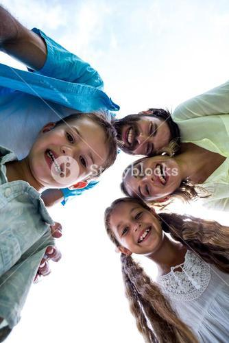 Cheerful family forming huddle against sky