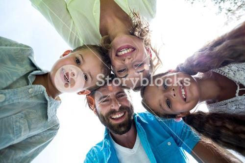 Smiling family forming huddle against sky