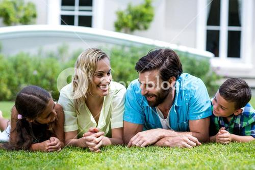 Smiling parents with children lying on grass in yard