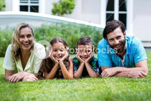 Portrait of happy family lying on grass at yard