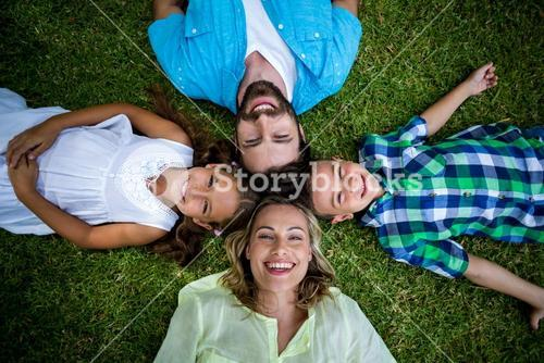 Happy family lying on grass in yard