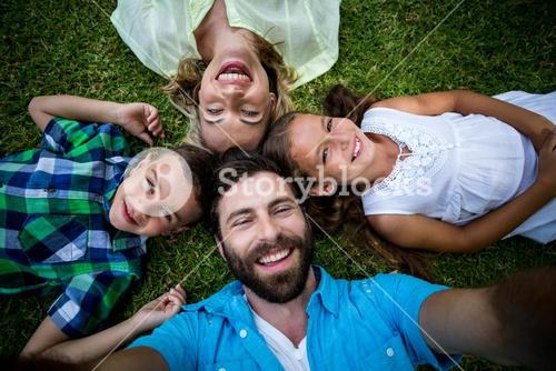 Cheerful family lying on grass in yard