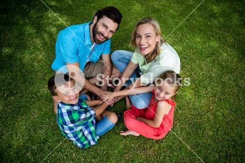 Family huddling hands while sitting on grass at yard