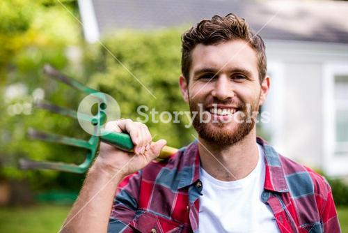 Portrait of man with rake standing in yard