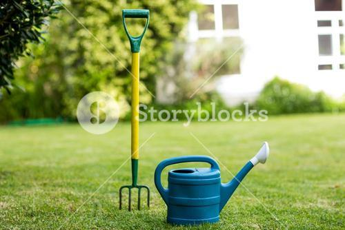 Close-up of rake and watering can in yard