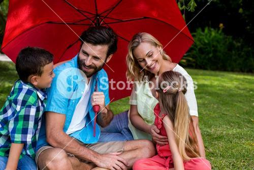 Family with umbrella sitting on grass at yard