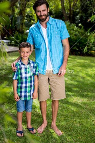 Father and son standing on grass in yard