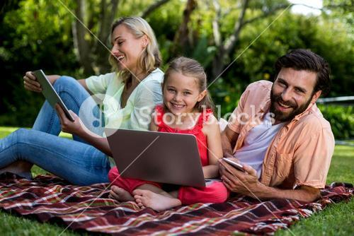 Family using technologies relaxing in yard