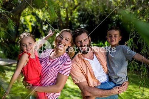 Happy parents carrying smiling children at yard