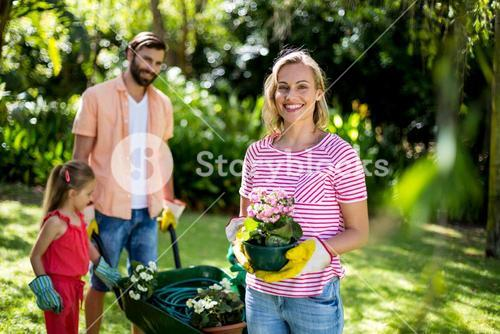 Woman holding flower pot with family at yard