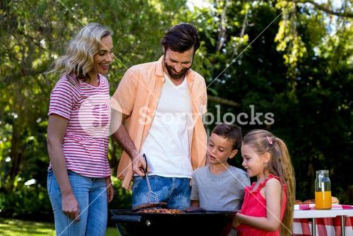 Family grilled food on barbecue at yard
