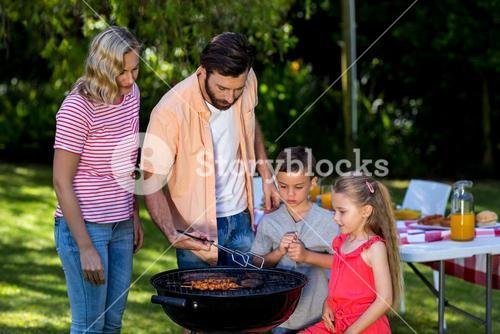 Family grilling food at barbecue in yard
