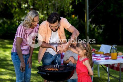 Father with mother teaching children to barbecue food