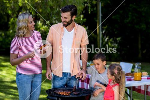 Mother and father with children cooking food at barbecue